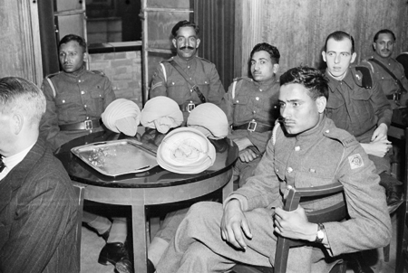 Private Mobed Shaffi of the Royal Indian Army Service Corps (RIASC) listens to the broadcast with some of his fellow soldiers around a table in the Hall of India, 1942