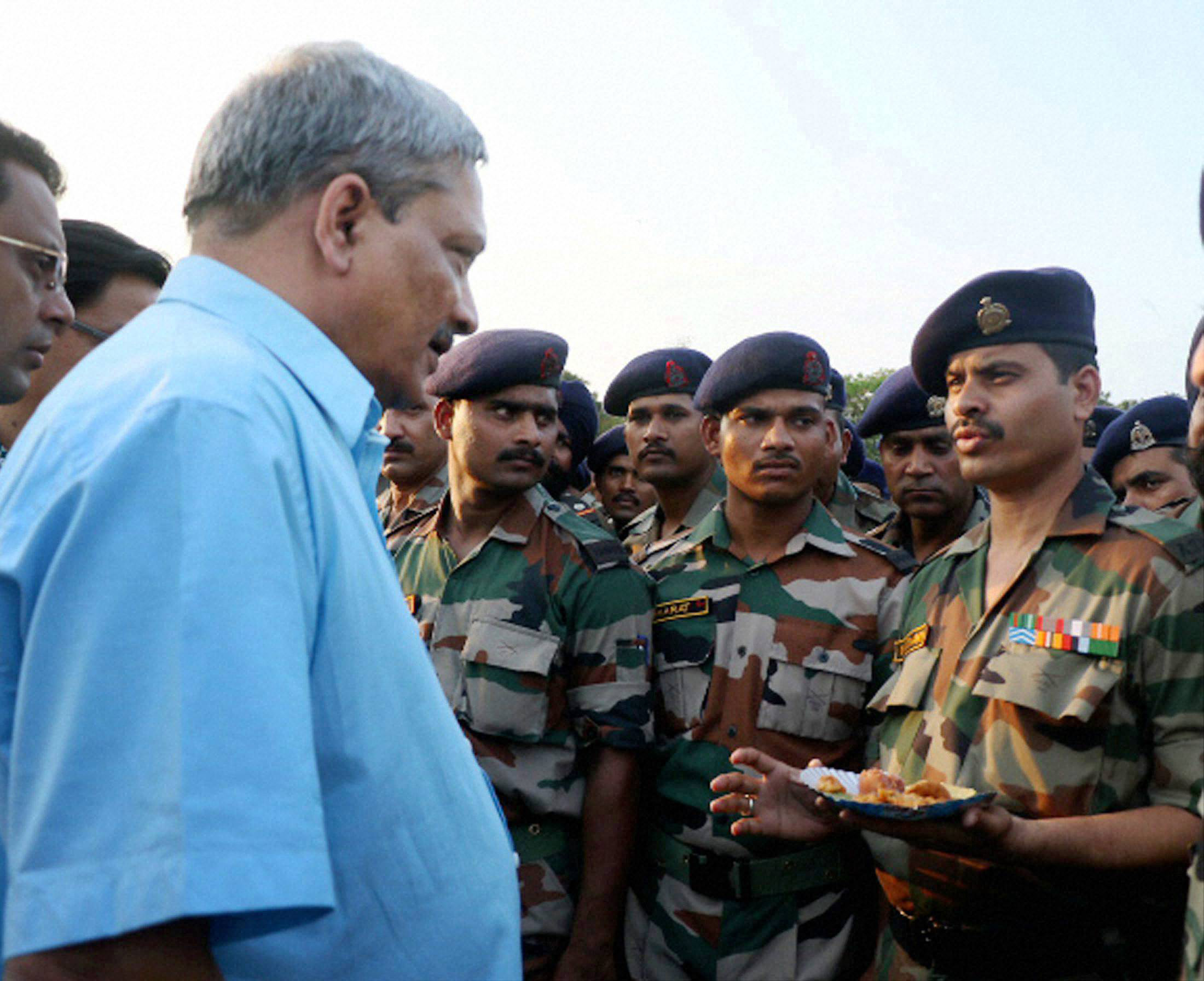 Defence Minister Manohar Parrikar interacting with troops over a cup of tea at Solmara Military Station in Tezpur on Friday. PTI Photo (PTI5_1_2015_000171B)
